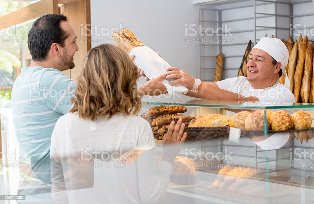 Baker serving a couple of customers at the bakery stock photo