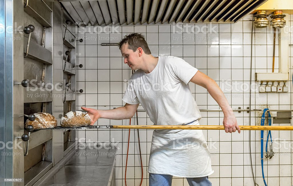 Baker taking bread out of oven stock photo