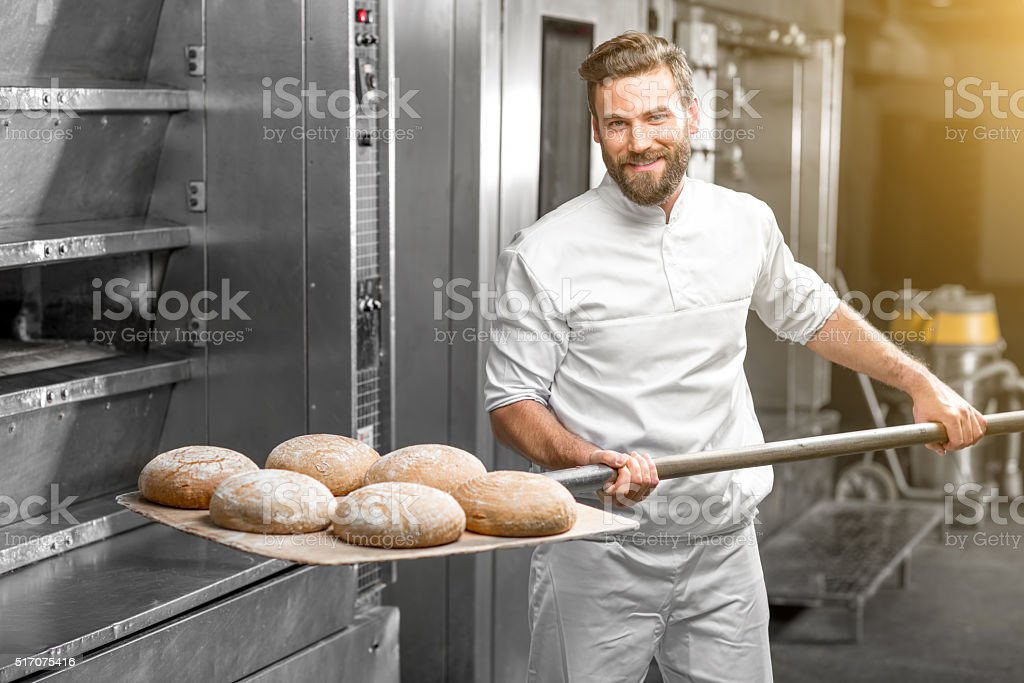 Baker taking out from the oven baked buckweat bread stock photo