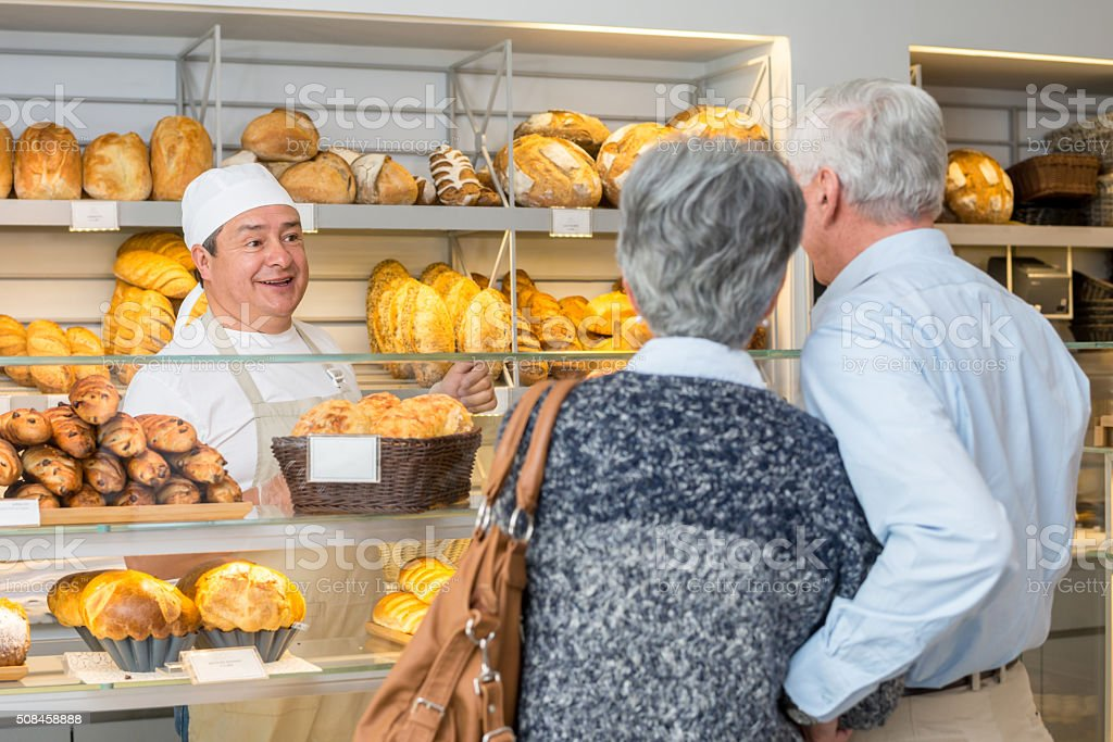 Baker talking to customers at the bakery stock photo