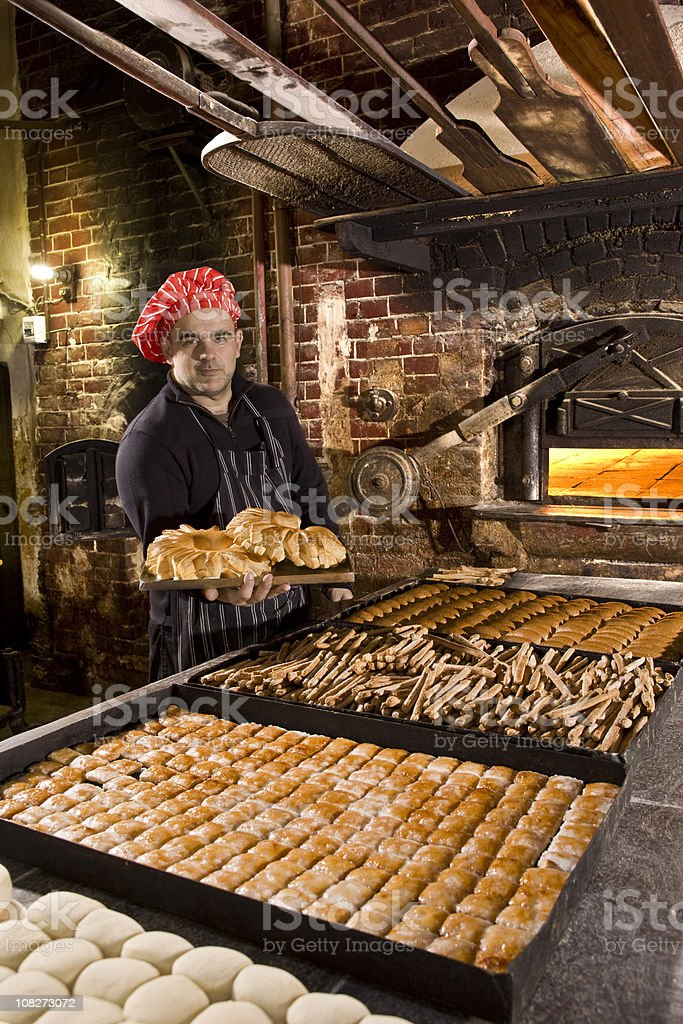 Baker with bread in antique bakery stock photo