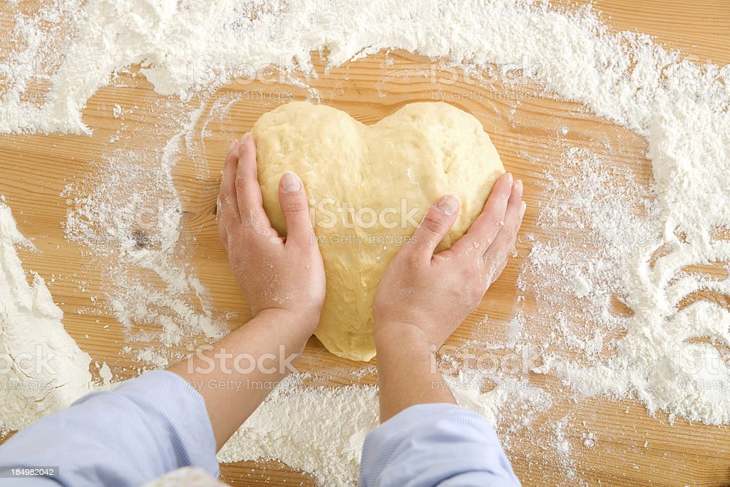 Baker's hands forming a heart from dough royalty-free stock photo