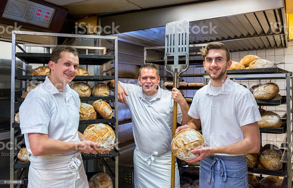 Bakers in their bakery, baking bread stock photo
