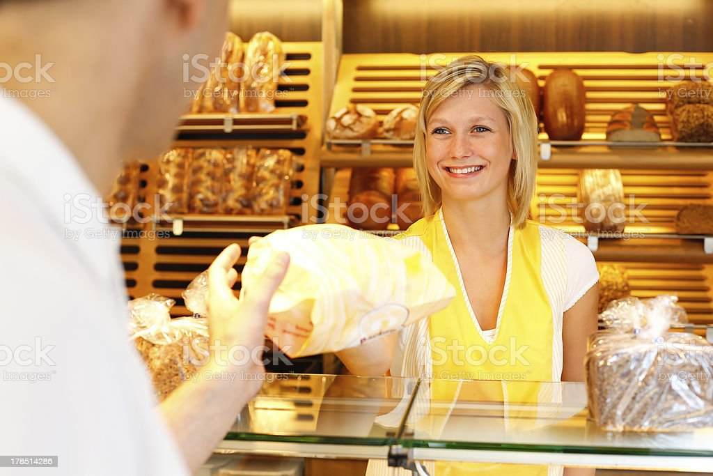 Baker's shop shopkeeper gives bread to customer royalty-free stock photo