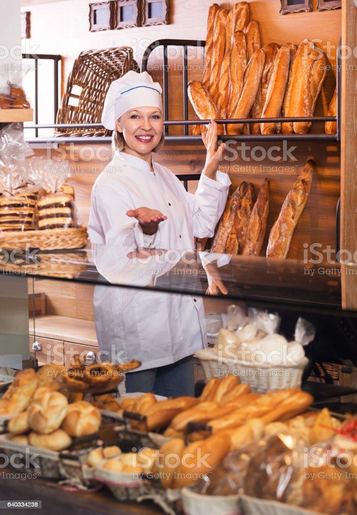 Bakery employee offering bread stock photo