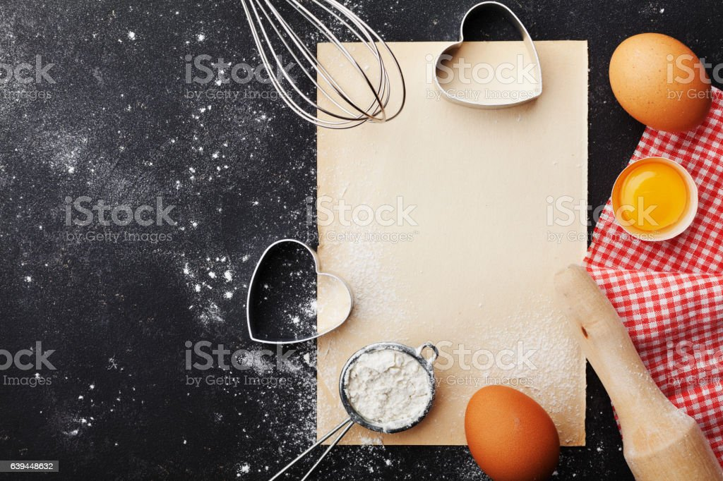 Baking background with flour, eggs, paper sheet, heart shape. stock photo