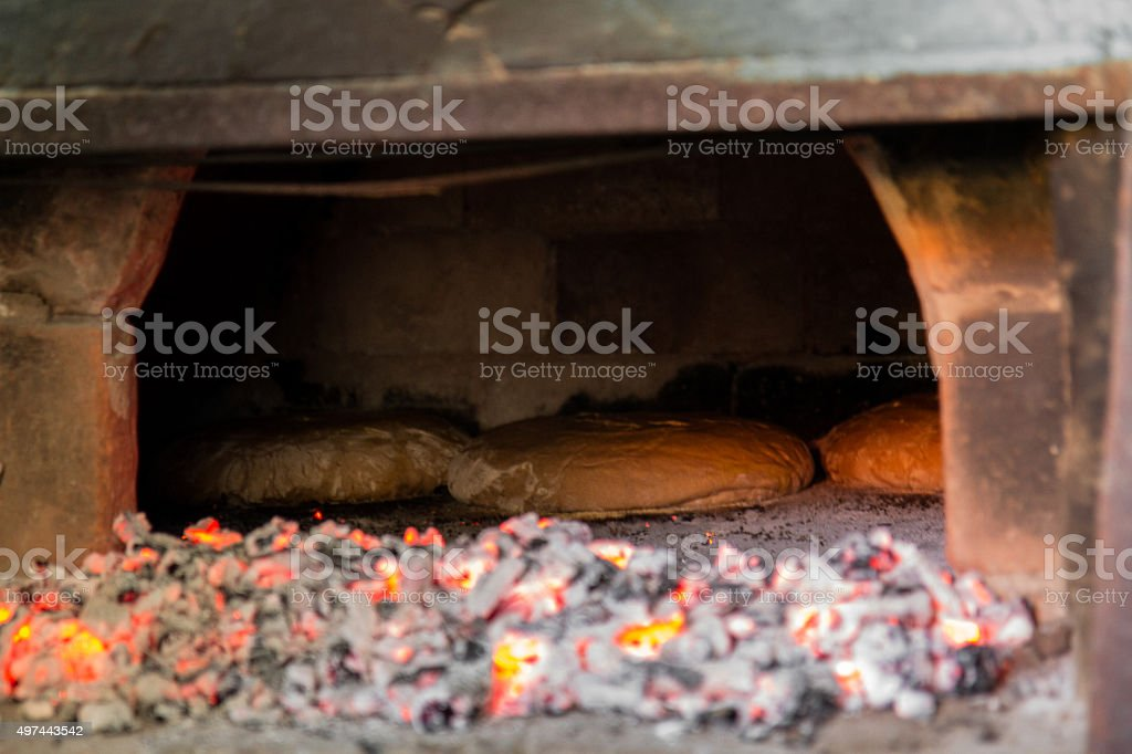 Baking bread in brick oven stock photo