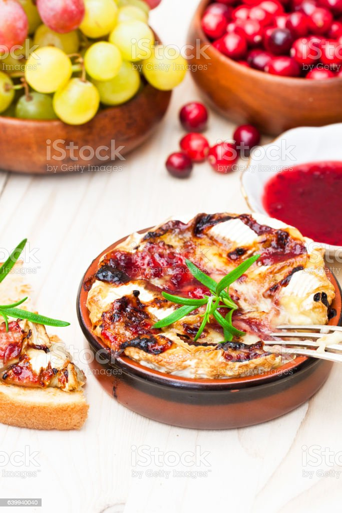 baking  camembert with cranberry sauce and rosemary served with stock photo