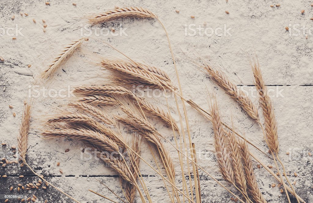 Baking concept on wood background, sprinkled flour with wheat ears stock photo