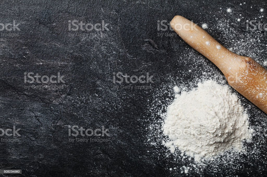Baking desk with flour and rolling pin, space for text stock photo