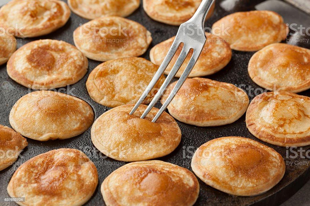 Baking Dutch mini pancakes called poffertjes stock photo