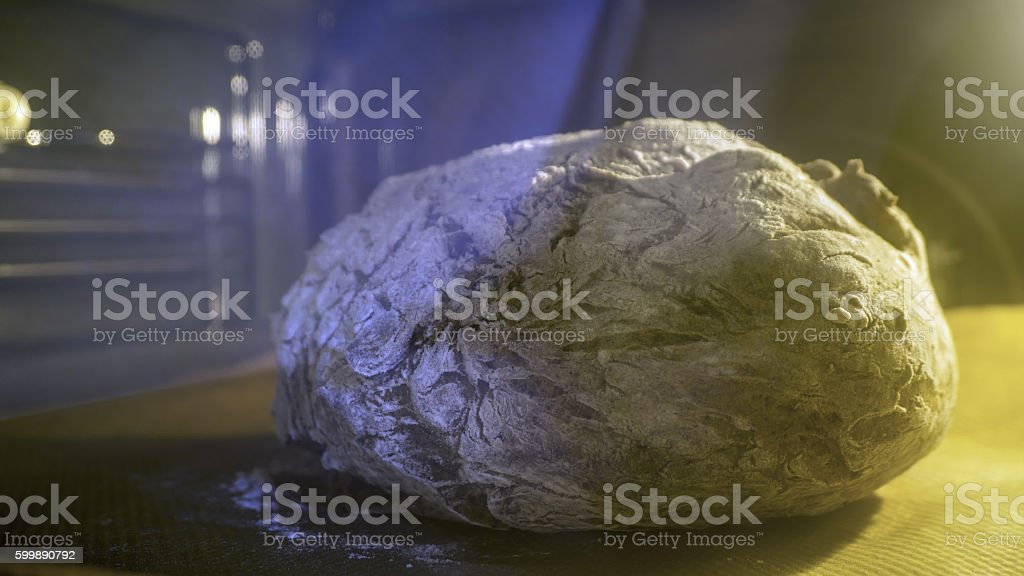 Baking homemade rye bread in the oven, yellow and blue stock photo