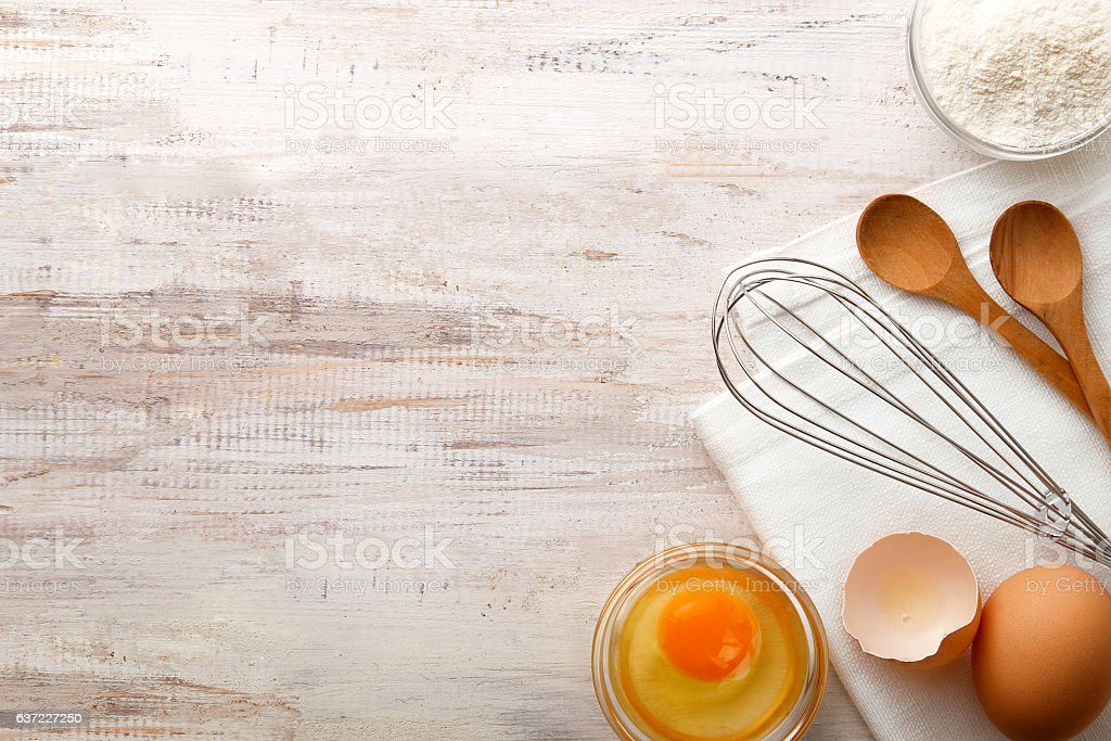 Baking ingredients flat lay on wooden background with copy space stock photo