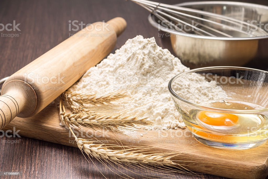 Baking ingredients with wheat ears on wood board royalty-free stock photo
