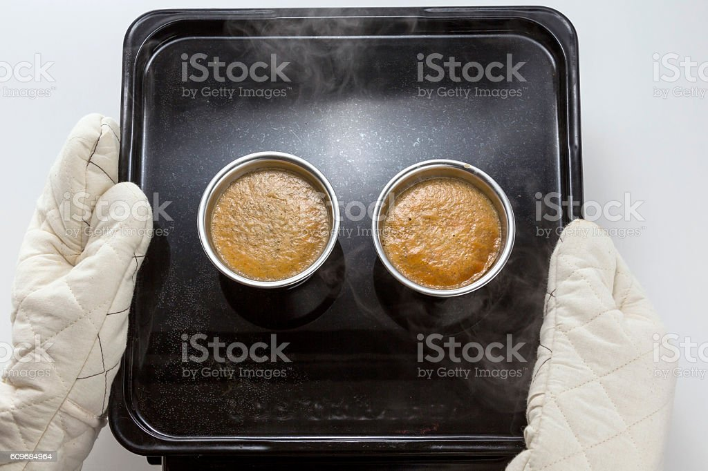 Baking muffin egg in cup by hands on black tray stock photo