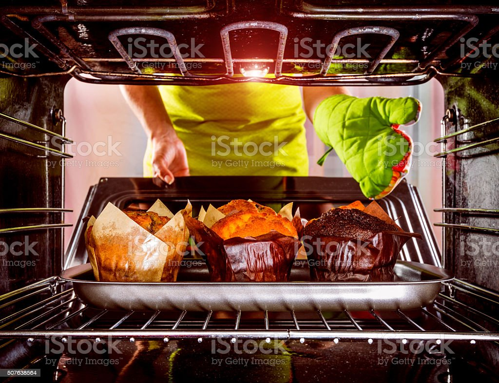 Baking muffins in the oven stock photo