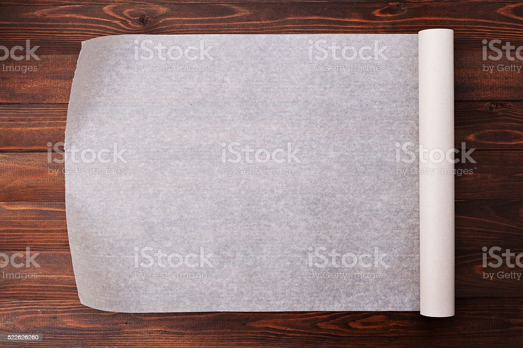Baking paper on wooden kitchen table for menu or recipes stock photo
