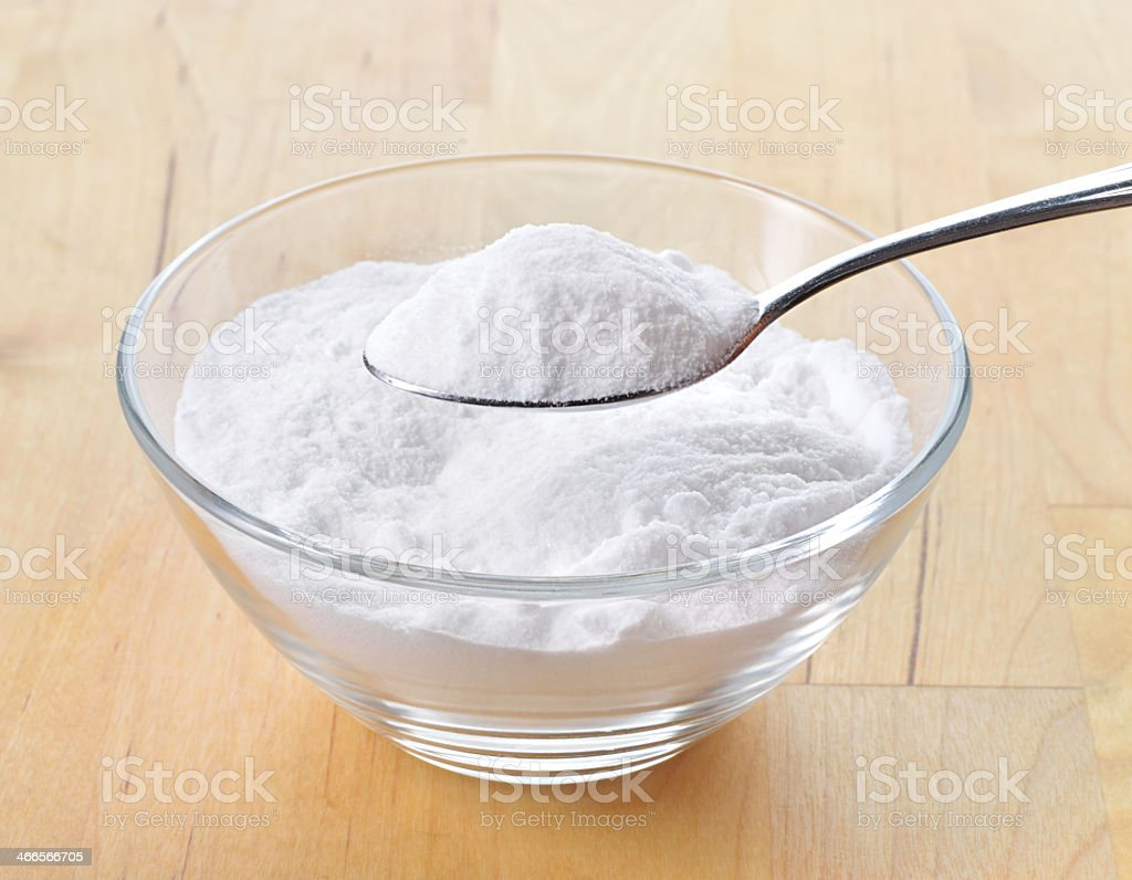 Baking soda in a glass bowl with one spoon stock photo