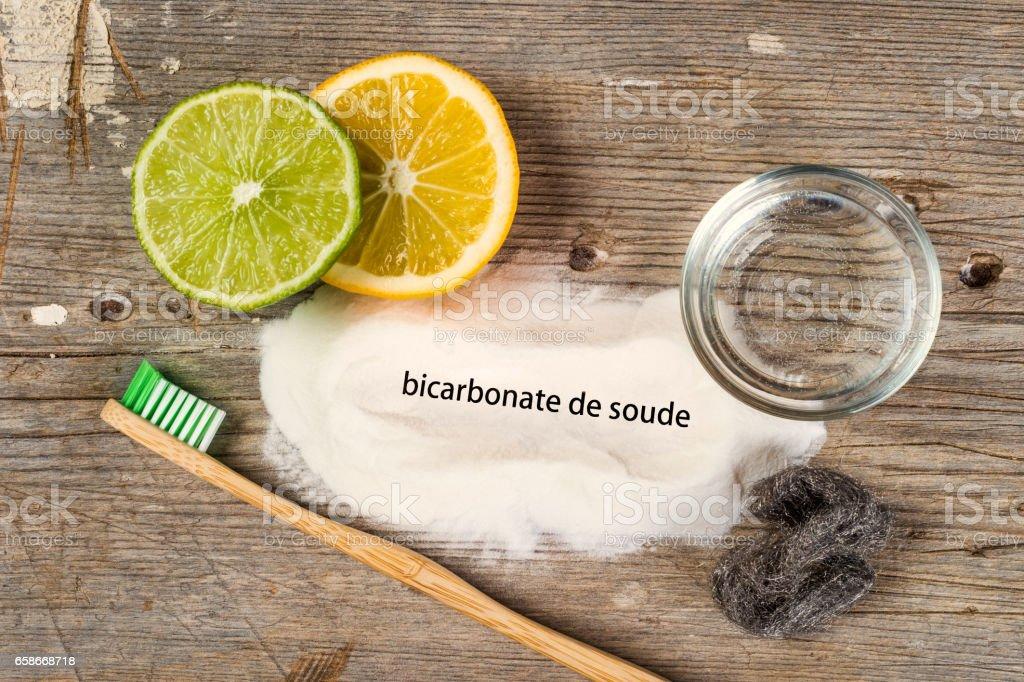 Baking soda, water, lemon, sponge, toothbrush and steel wool - Bicarbonate de soude means baking soda in french. stock photo