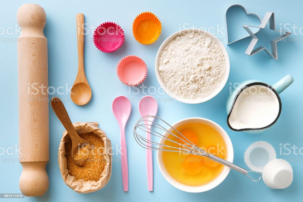 Baking utensils and ingredients. Egg yolk, brown sugar, milk, flour, whisker, spoons, cinnamon, bowl, rolling pin, cupcake paper cup, molds, sweet decoration elements. Top view. Flat lay stock photo
