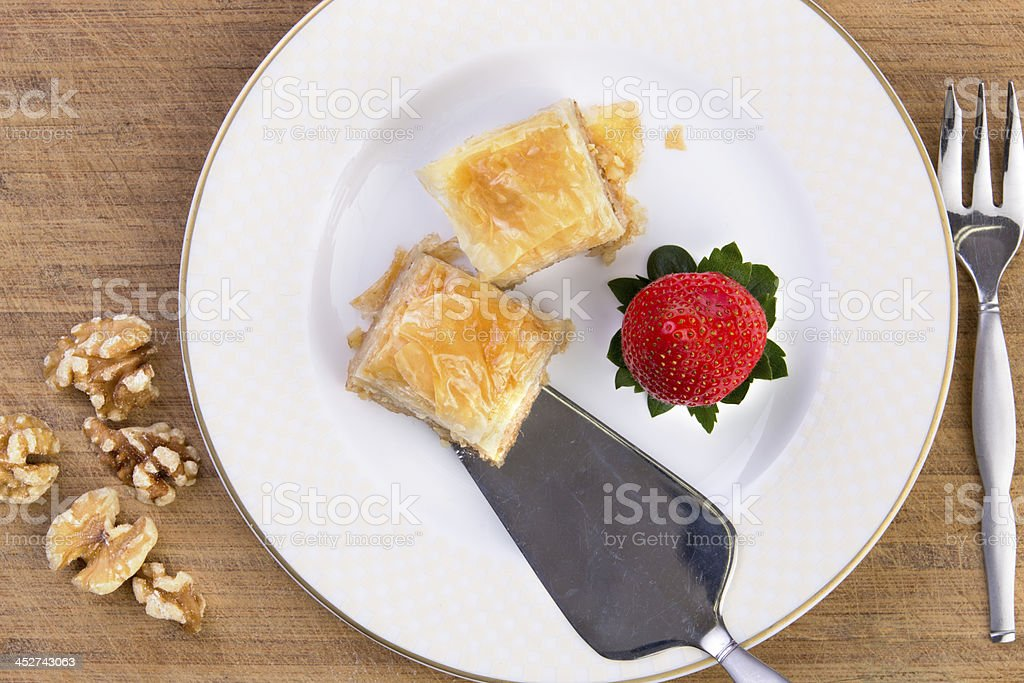 Baklava Served with Spatula on Bamboo Cutting Board royalty-free stock photo
