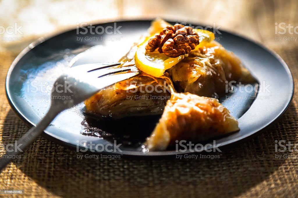 Baklava with a slice of lemon and walnut on top stock photo