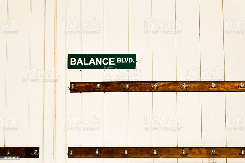 Balance Boulevard Street Sign above Clothes Hooks stock photo