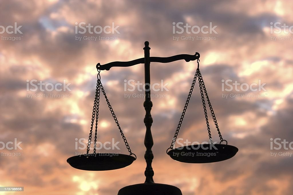 Balance Scale Against Multi-Colored Sky stock photo
