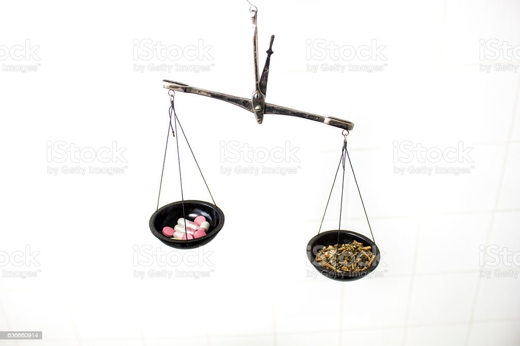 balance scale with pills and herb stock photo