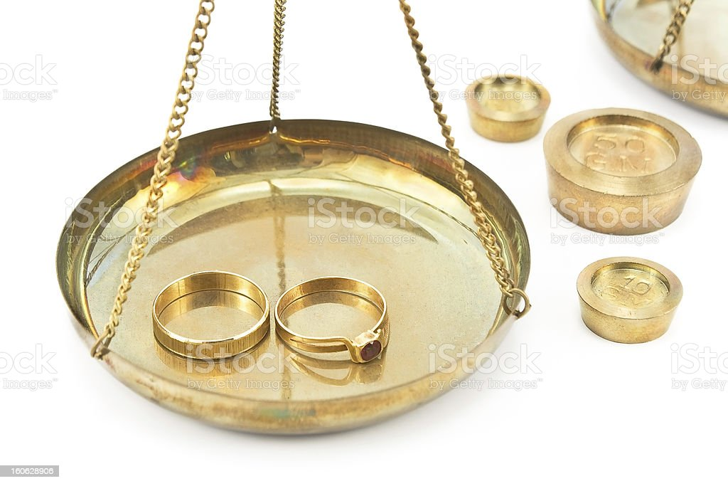 Balance scales with golden wedding rings royalty-free stock photo
