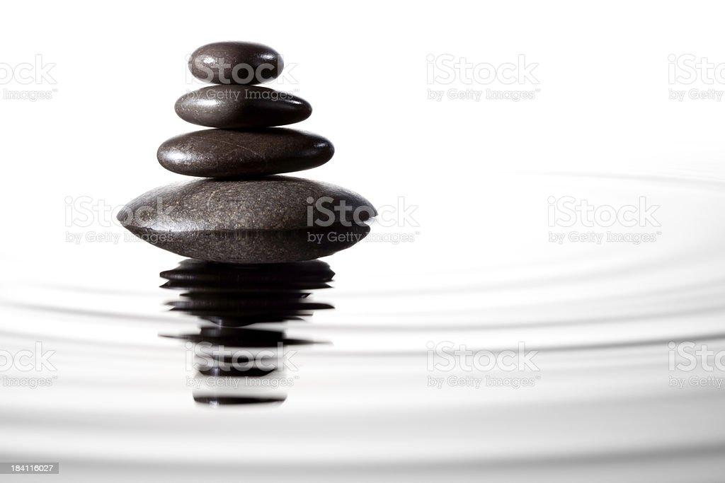 Balanced black stones in water - Feng Shui Massage Lastone stock photo