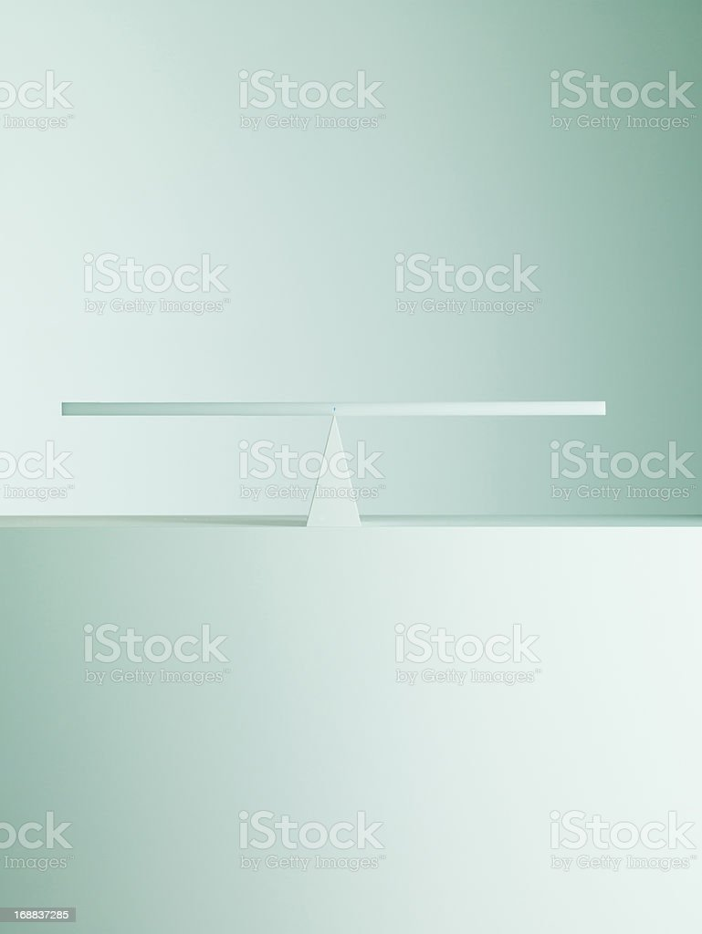 Balanced on opposite ends of seesaw stock photo
