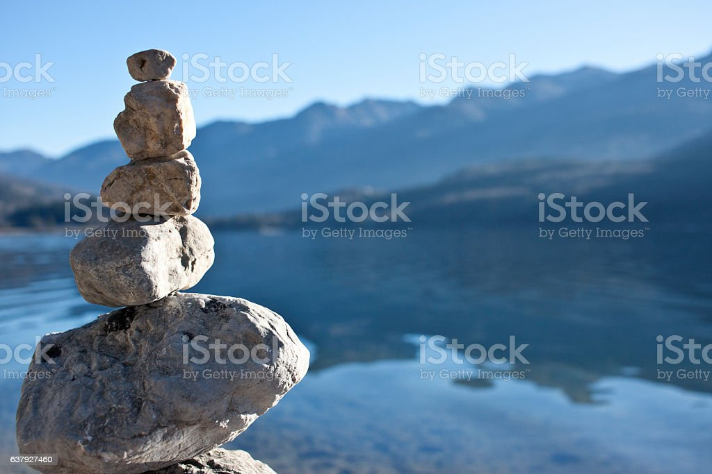 Balanced rocks on a lake in the mountains stock photo