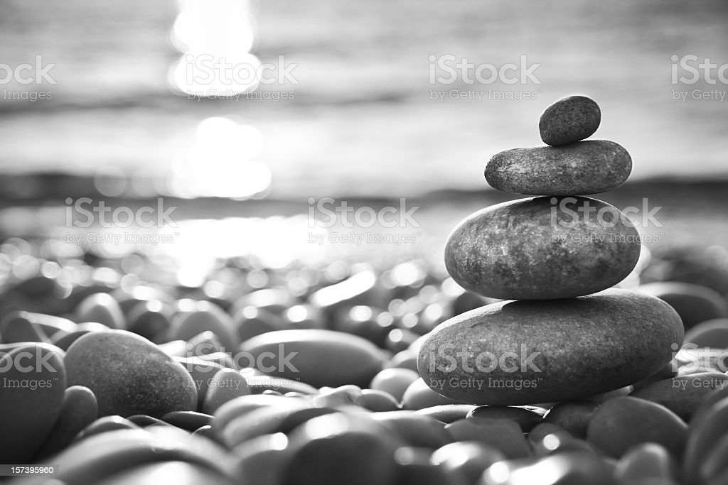 Balanced stones on a beach - black and white photography stock photo