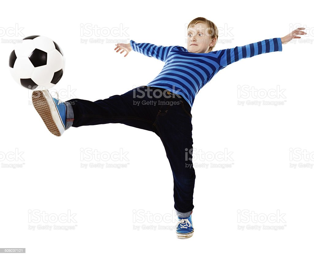 Balancing act as schoolboy footballer kicks ball, leaning backwards stock photo