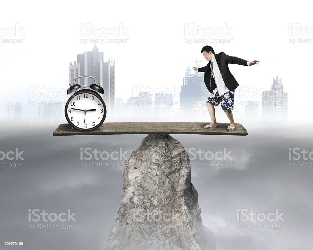 Balancing against alarm clock on board at hilltop stock photo