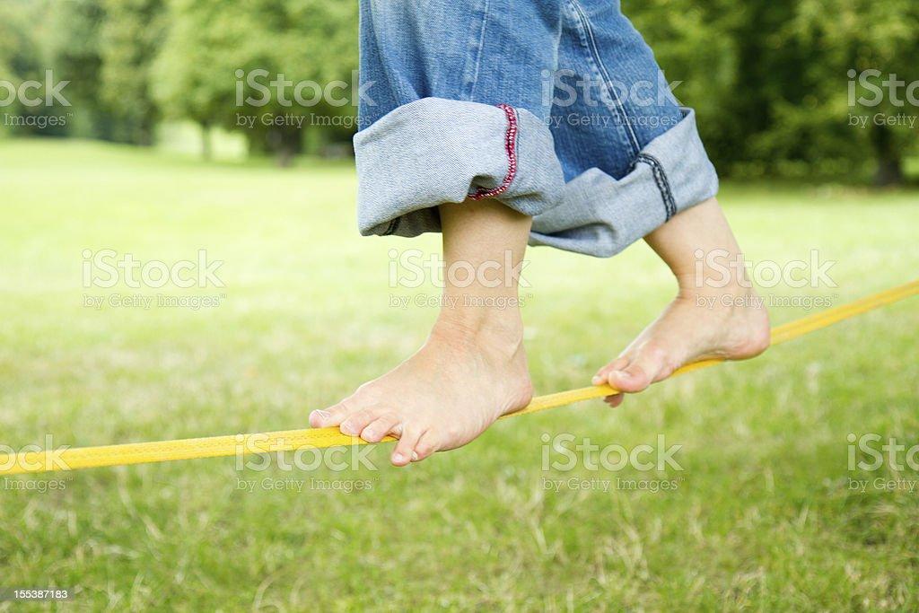 Balancing barefoot on a Slackline stock photo