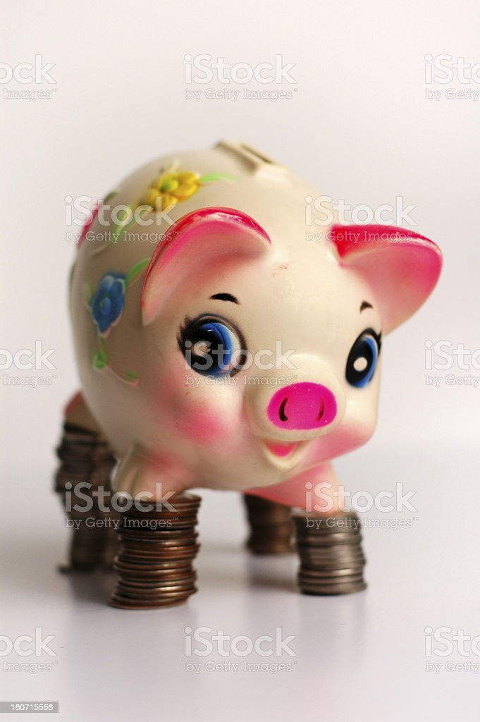 Balancing Finances - Happy Piggy Bank Standing on Coins royalty-free stock photo