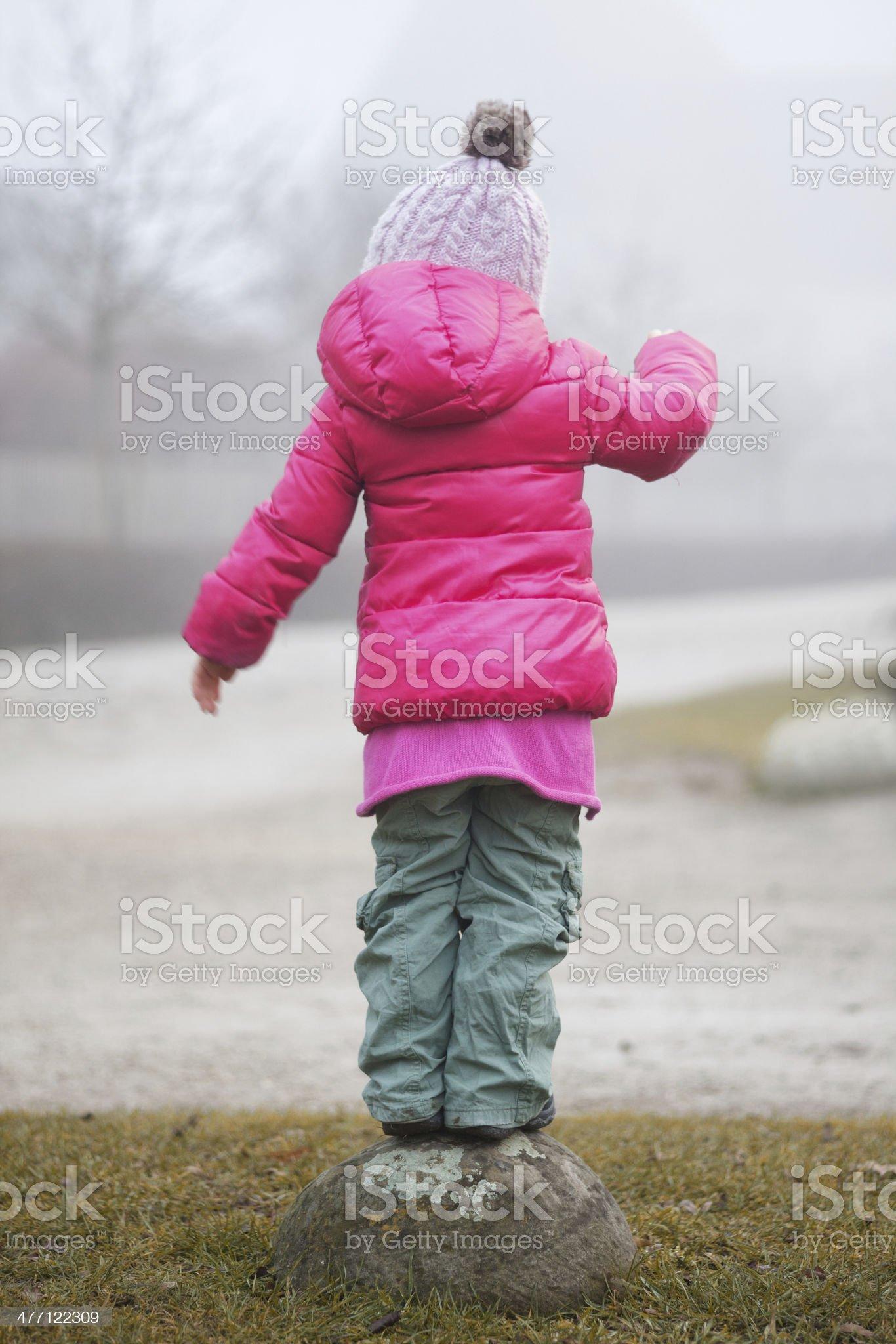 Balancing girl from behind royalty-free stock photo