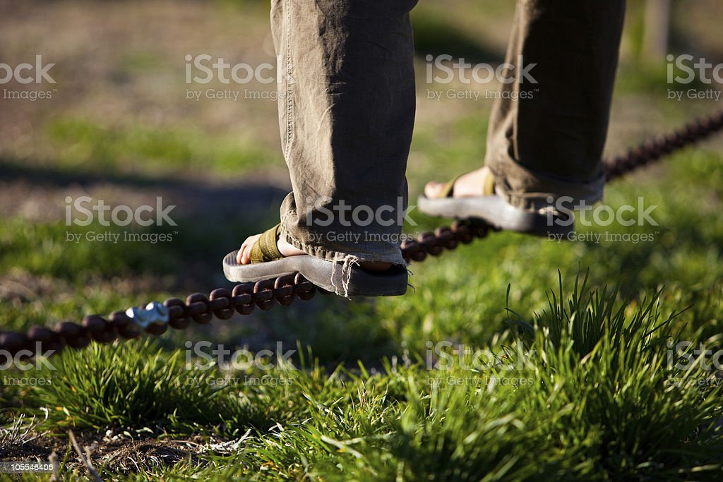 Balancing on Chain wearing Sandals stock photo