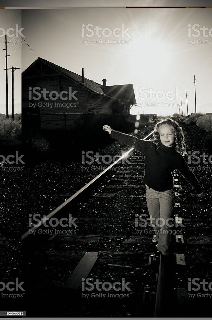 balancing on railroad track stock photo