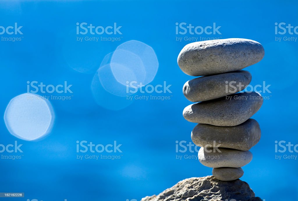 Balancing pebbles on blue background royalty-free stock photo