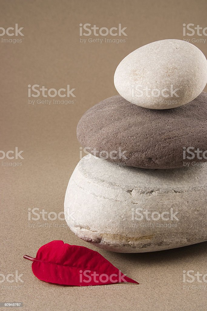 Balancing pebbles with a red leaf stock photo