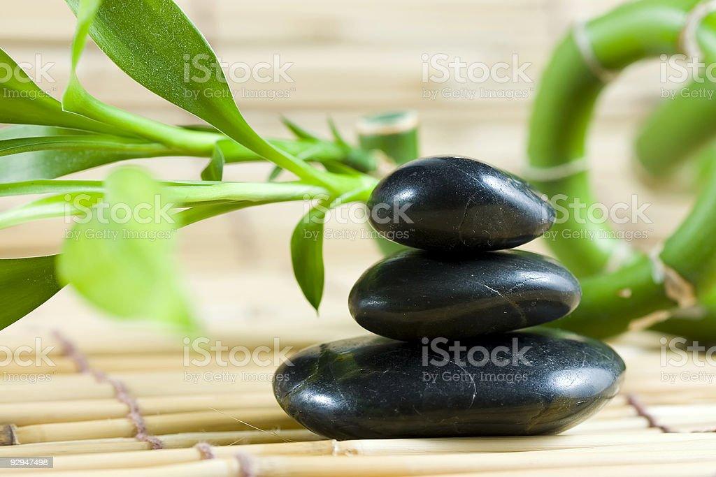 Balancing pebbles with bamboo stock photo
