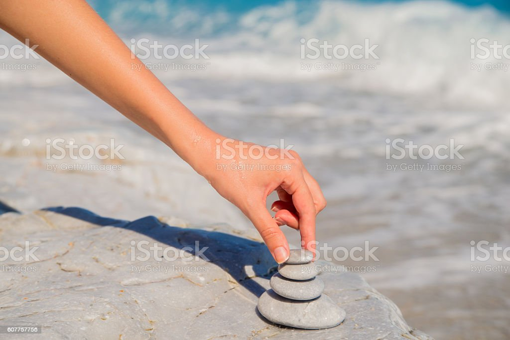 balancing stone,  Person stacking last rock on pebble tower stock photo