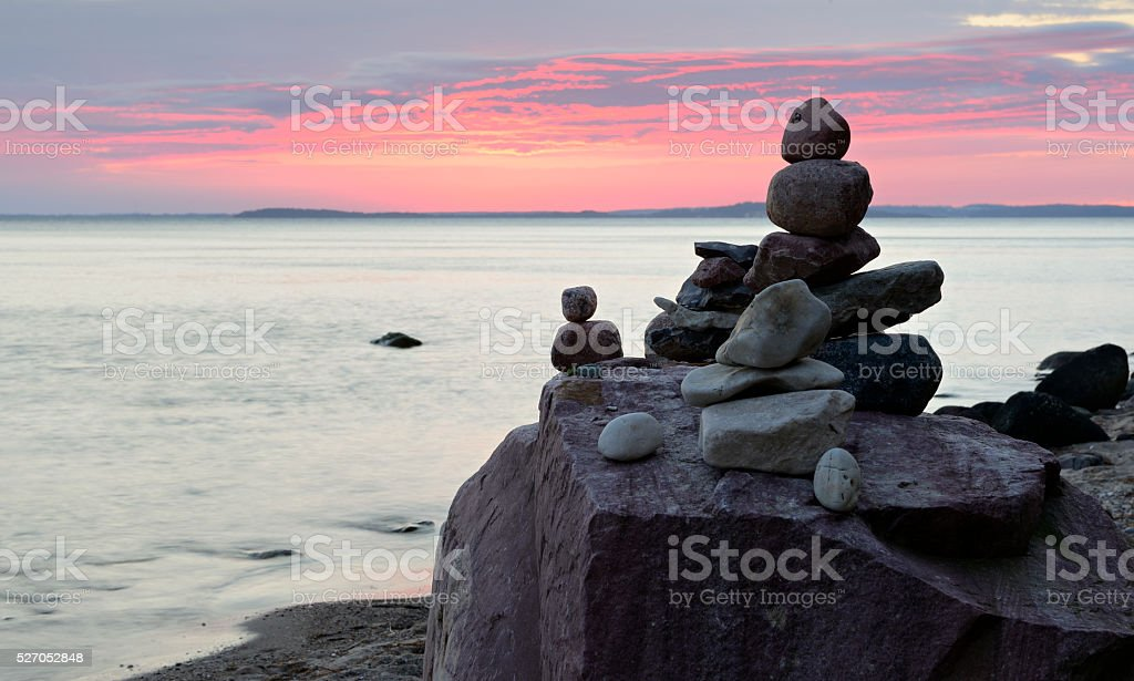 Balancing Stones on Sand Beach with Huge Boulders at Sunset stock photo
