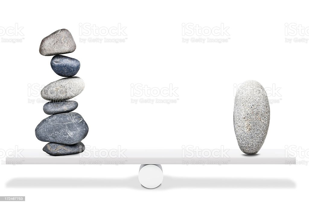 Balancing stones on seesaw stock photo