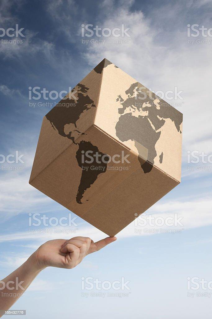 Balancing worldwide trade cardboard box and world map royalty-free stock photo