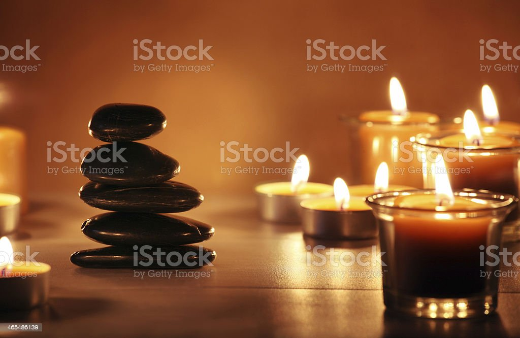 Balancing zen stones and pebbles with candles on wooden table stock photo