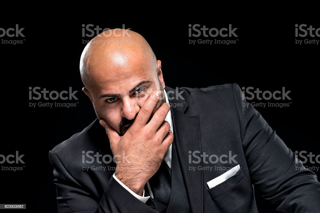 bald businessman with black beard looking pensive stock photo